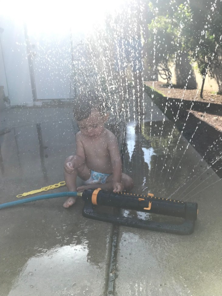 Toddler boy play with water sprinklers in the backyard