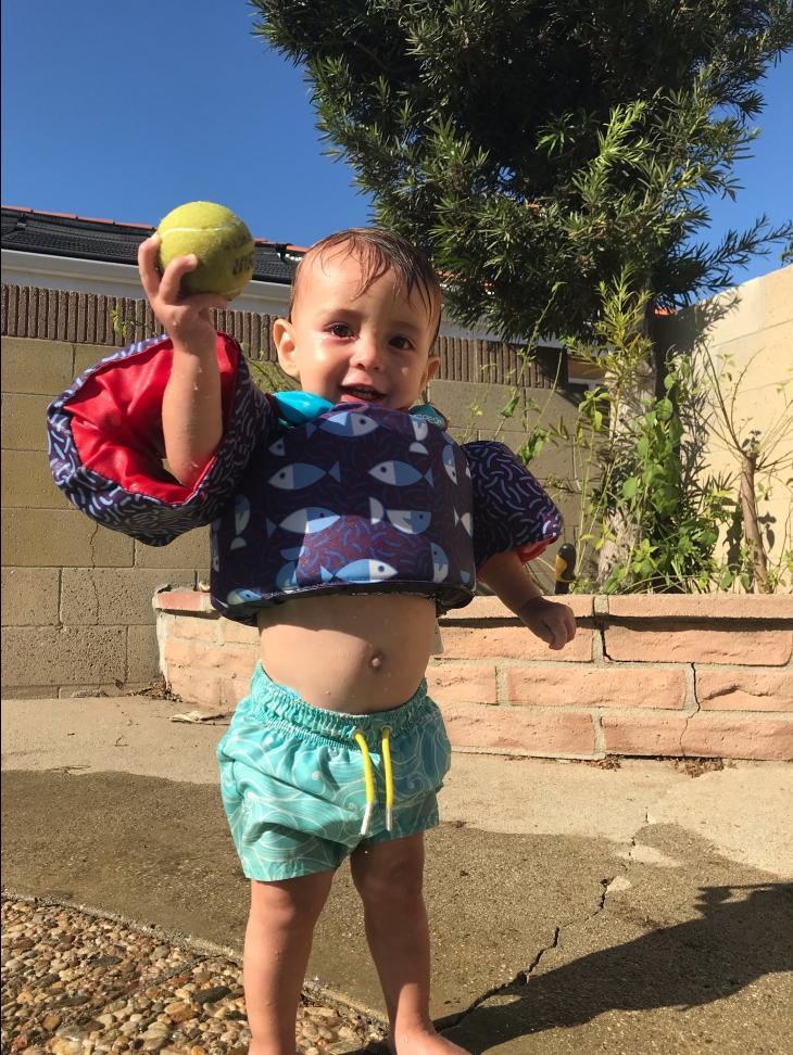 Toddler boy in swim trunks throwing tennis ball in pool