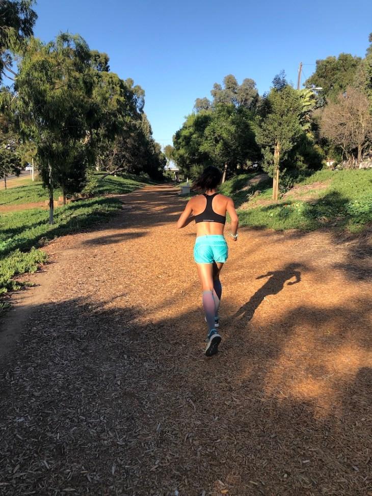 Female runner running in sports bra on running trail.