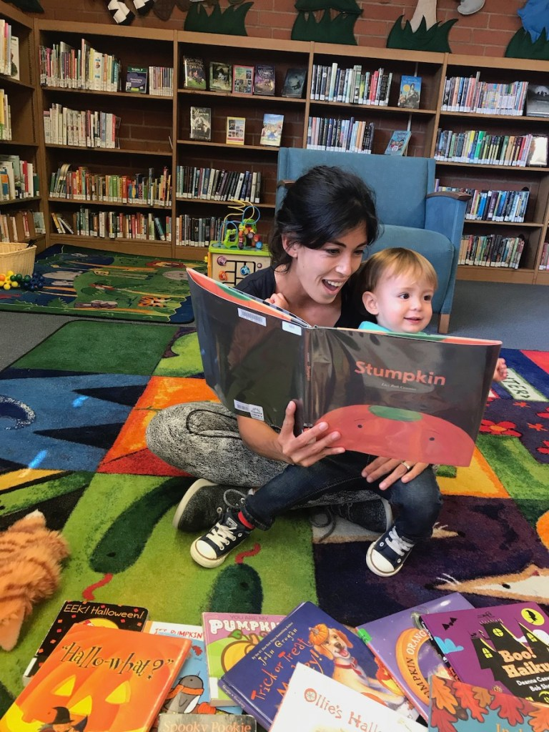 mother reading Stumpkin book to her toddler boy at the local library