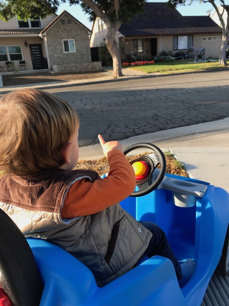 toddler boy in blue push car pointing out to Halloween decorations on a house