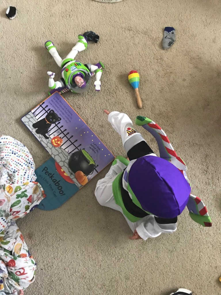 toddler boy dressed in Buzzlightyear costume for Halloween with a buzzlightyear toy from Disneyland