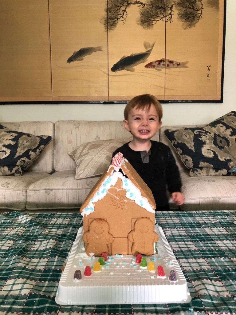 toddler smiling with gingerbread house