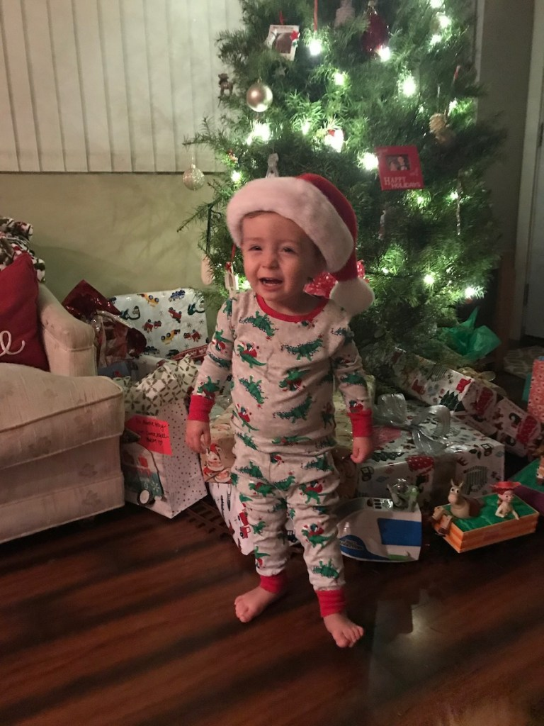 toddler with santa hat smiling by Christmas tree