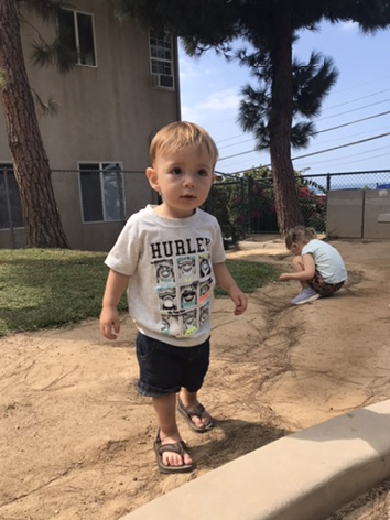 Toddler boy wearing Hurley T-shirt with leather sandals at the park