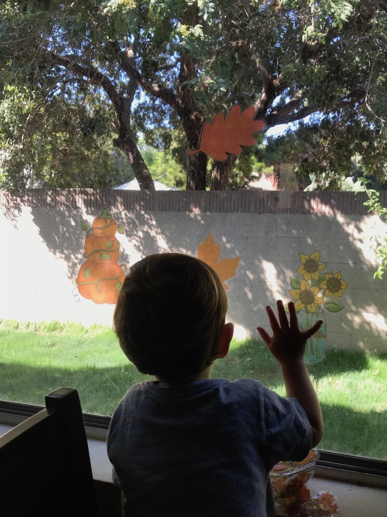 toddler boy decorating window with fall window stickers
