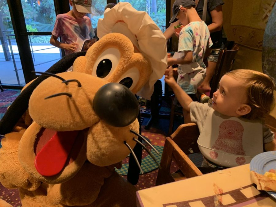 toddler eating with Pluto character at Goofy's Kitchen at Disneyland Hotel