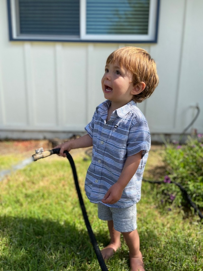 toddler boy watering grass